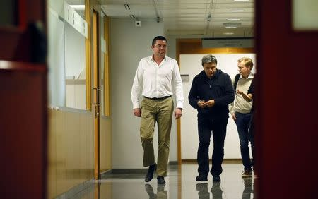 McLaren's team manager Eric Boullier and physiotherapist Fabrizio Borra walk at a corridor in the hospital where McLaren Formula One driver Fernando Alonso of Spain is hospitalized, in Sant Cugat