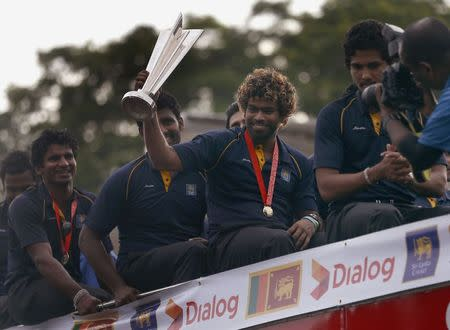Sri Lanka's Twenty20 cricket captain Malinga shows the 2014 T20 trophy after they arrived at the Bandaranaike International Airport in Katunayake