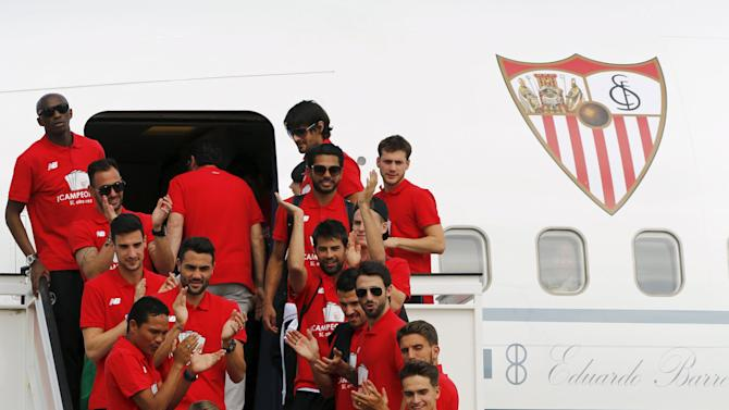 Sevilla's team celebrates with their Europa League trophy after landing in the Andalusian capital of Seville, southern Spain