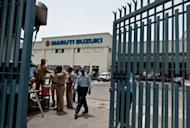 Police and security guards stand at the gate at the Maruti Suzuki Production Facility in Manesar, on July 19,2012. Japan has condemned violence at a Maruti Suzuki car plant near New Delhi that claimed the life of an executive and left over 80 employees including two Japanese injured