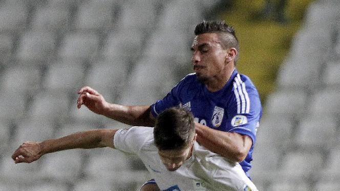 Cyprus' Constantinos Charalambides, rear, challenges for the ball with Andraz Struna of Slovenia during their World Cup group E qualifying soccer match at GSP stadium in Nicosia, Cyprus, Tuesday, Sept. 10, 2013