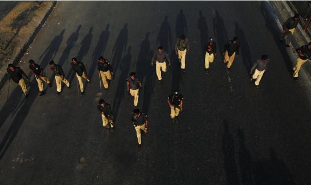 Policemen march on the road as supporters of Jamaat-e-Islami and the Pakistan Tehreek-e-Insaf political party participate in a protest in Karachi