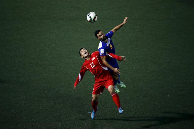 Manuel Ott of Philippines and Jon Kwang-ik of North Korea jump for ball during team's preliminary 2018 World Cup and 2019 AFC Asian Cup qualifying soccer match at the Kim Il Sung Stadium in Pyongy