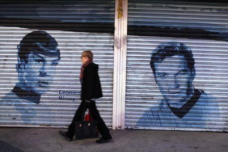 Pedestrian walks past pictures of original Star Trek actors Nimoy and Shatner painted onto store front security gates on Hollywood Boulevard