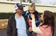 Oroville, Calif., resident Patrick Cumings, left, holds his daughter, Elizabeth, and he stands with his wife, Elizabeth Cumings at the Red Cross evacuation center in Chico, Calif., Monday, Feb. 13, 2017. The water level has dropped behind the Oroville Dam, nation's tallest dam, in Oroville reducing the risk of a catastrophic spillway collapse and easing fears that prompted the evacuation of the Cumings and others downstream. (AP Photo/Don Thompson)