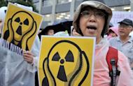 "People shout slogans during a demonstration denouncing nuclear power plants, on July 20. Thousands of people are expected to form a ""human chain"" around Japan's parliament on Sunday as part of demonstrations aimed at ending nuclear power after last year's atomic crisis at Fukushima"