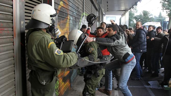 Protesters clash with riot police outside the Labor Ministry in Athens, Wednesday, Jan. 30, 2013. Protesters from a Communist-back labor union forced their way into a government building and clashed with police who used tear gas to expel them. Members of the union are protesting planned reforms to the country's pension and income contribution system — part of ongoing austerity cuts demanded by Greece's euro partners and the International Monetary Fund who are keeping the country afloat with emergency loans. (AP Photo/Thanassis Stavrakis)