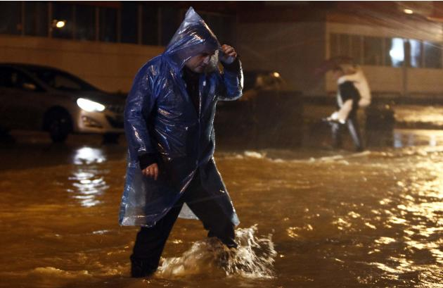 A man walks along a flooded street in Sochi
