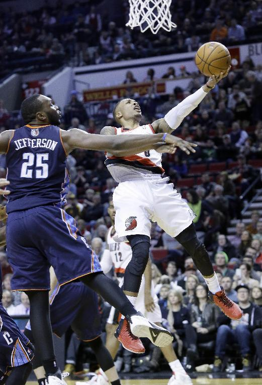 A Portland Trails Blazers guard Damian Lillard, right, goes to the basket against Charlotte Bobcats center Al Jefferson during the second half of an NBA basketball game in Portland, Ore., Thursday, Jan. 2, 2014.  Lillard scored 24 points as they beat Charlotte 134-104