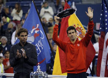 Rafael Nadal of Spain applauds as Novak Djokovic of Serbia raises his runner up trophy after Nadal won their men's final match at the U.S. Open tennis championships in New York, September 9, 2013. REUTERS/Ray Stubblebine
