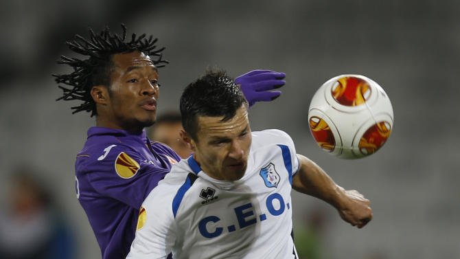 Fiorentina's Juan Cuadrado, left, and Pandurii's Bogdan Ungurusan, right, challenge for the ball during an Europa League, group E match, between Fiorentina and Pandurii, at the Cluj Arena stadium in Cluj, Romania, Thursday, Nov. 7,  2013