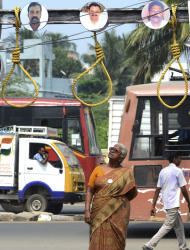 In this Monday Oct.10, 2011, photo, Arputhammal , the mother of Arivu Perarivalan, one of the three convicted in the 1991 assassination of former Indian Prime Minister Rajiv Gandhi, looks at symbolic nooses at the venue of a relay hunger protest, where people from different Tamil organization gather daily to protest against the death penalty, in Chennai, India. Across most of India the three men on death row in the assassination of Gandhi are reviled as murderous traitors to the nation. But ethnic Tamils in southern India see things very differently. Nearly every major public figure has demanded clemency, sparking a political storm fueled by emotions still raw from the gory 2009 routing of Sri Lanka's Tamil rebels, who ordered the killing. ( AP Photo/ Nathan G.)