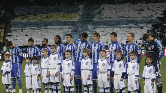 Players of Dynamo Kiev stand before their national championship soccer match against Tavriya Simferopol as football fans display a Ukrainian Navy flag in Kiev