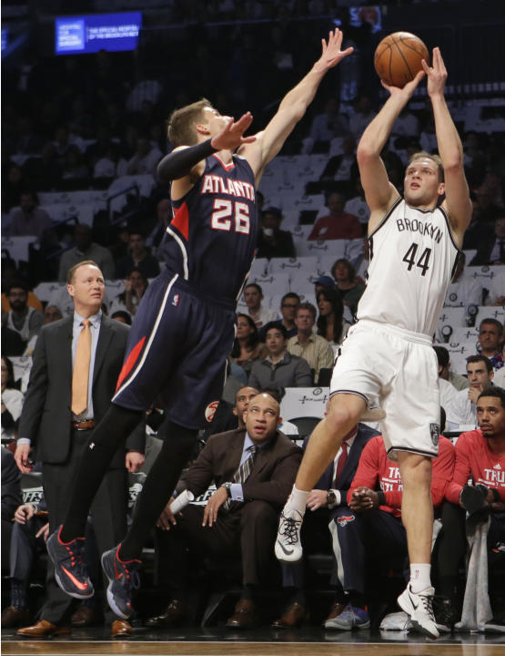 Atlanta Hawks head coach Mike Budenholzer, left watches as guard Kyle Korver (26) defends Brooklyn Nets guard Bojan Bogdanovic (44), who takes a three-point shot in the first quarter of Game 4 of a fi