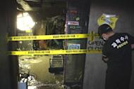 Handout photo from the Busan Metropolitan Police Agency shows a policeman at the site of a karaoke lounge fire in the South Korean city of Busan on May 5. A fierce blaze swept through the karaoke lounge on Saturday night, killing nine people including three Sri Lankans, police said on Sunday
