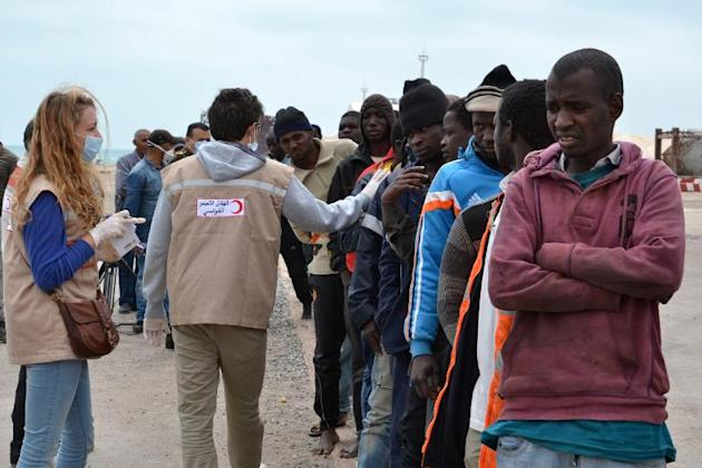 Illegal migrants stand next to members of the Red Crescent in the southeastern Tunisian port city of Zarzis on April 25, 2015, after they were rescued by fishermen when their boat got into difficultie