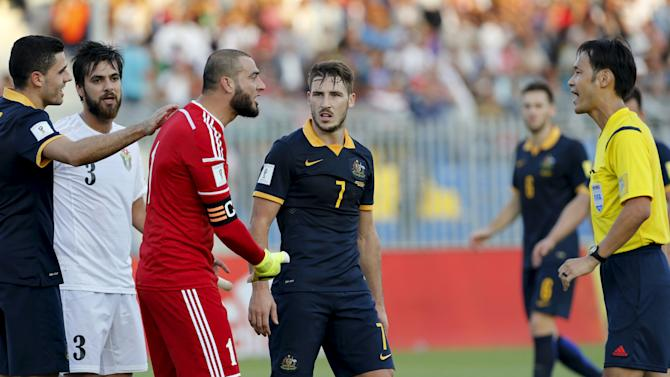 Jordan's goalkeeper Amer Shafi speaks to Japanese referee Masaaki Toma in the presence of Australia's Mathew Leckie in Amman