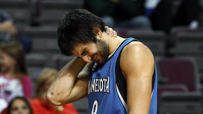 Minnesota Timberwolves guard Ricky Rubio (9), of Spain, reacts on his way to the bench after being hit in the second half of their preseason NBA basketball game against the Detroit Pistons in Auburn Hills, Mich., Thursday, Oct. 24, 2013
