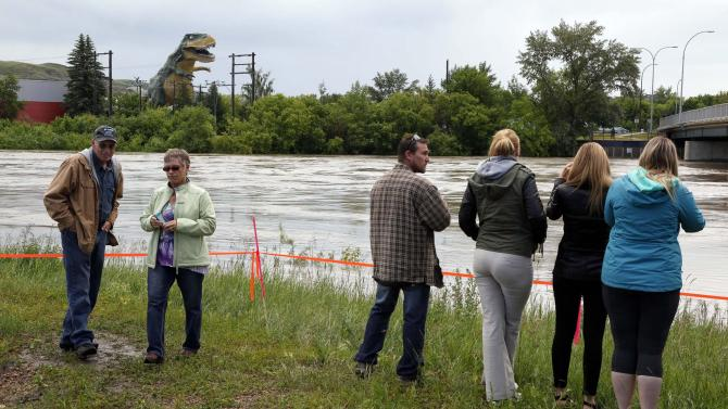 Onlookers watch the swollen Red Deer River in Drumheller, Alberta, Sunday, June 23, 2013. The town is bracing for the worst after heavy rains have caused flooding, closed roads, and forced evacuation across southern Alberta. (AP Photo/The Canadian Press, Jeff McIntosh)