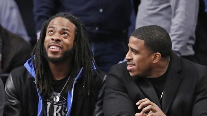 Seattle Seahawks cornerback Richard Sherman, left, and linebacker Bobby Wagner watch the Toronto Raptors in the first half of an NBA basketball game against the Brooklyn Nets at the Barclays Center, Monday, Jan. 27, 2014, in New York