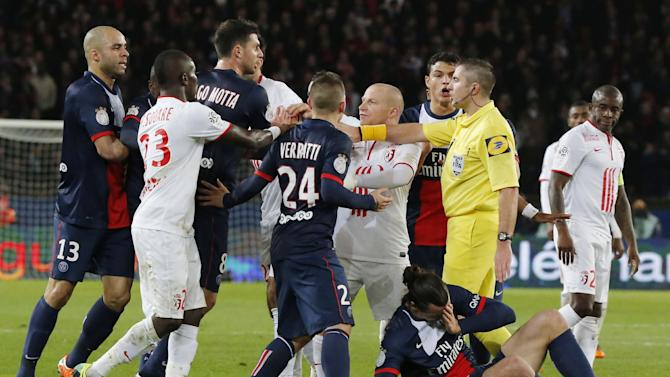 Paris-Saint-Germain's and Lille's players argue with referee Fredy Gautrel, second from right, while Lille's Antonio Mavuba, right, looks at Zlatan Ibrahimovic of Sweden as he lies on the ground during a French league one soccer match between Paris-Saint-Germain and Lille at Parc des Princes stadium in Paris, Sunday Dec. 22, 2013. Ibrahimovic and Mavuba were booked for shoving each other