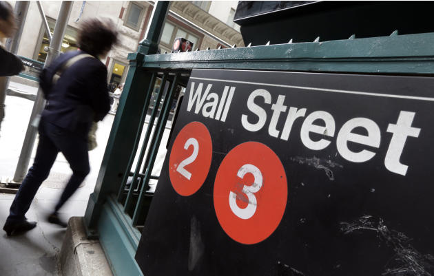 FILE - In this Oct. 2, 2014 file photo, people pass a Wall Street subway stop, in New York's Financial District. U.S. stocks moved lower in early trading Tuesday, March 31, 2015, erasing some gain