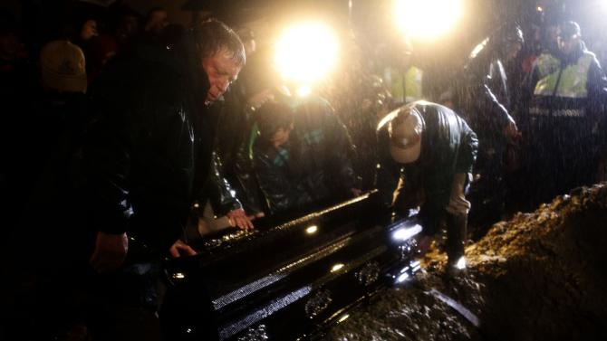 The coffin of Portuguese soccer great Eusebio is lowered into the ground at Lumiar cemetery in Lisbon