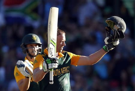 South Africa's captain AB de Villiers is applauded by team mate Farhaan Behardien as he celebrates reaching his century during the Cricket World Cup match against the West Indies at the CG