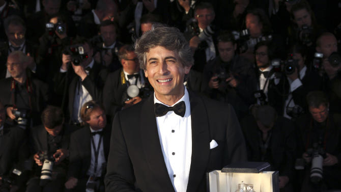 Director Alexander Payne, on behalf of actor Bruce Dern, poses with the Best Actor award for Dern's role in the film Nebraska during a photo call after an awards ceremony at the 66th international film festival, in Cannes, southern France, Sunday, May 26, 2013. (Photo by Joel Ryan/Invision/AP)