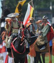 People clad in samurai costumes play the triton on horseback during a parade at the annual Soma Nomaoi festival in Minamisoma. Clad in decorated helmets and carrying traditional Japanese swords, participants swaggered about on horseback followed by a feudal lord's procession decorated with colourful banners displaying their family crests