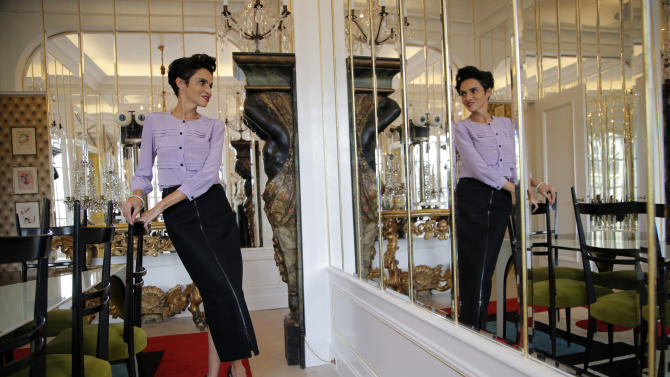 In this photo taken Wednesday, Oct. 17, 2012, Farida Khelfa, the muse of the Schiaparelli house, poses at the Schiaparelli apartment in Paris. While Schiaparelli is no longer a household name - her business folded in 1954 - her mould-breaking designs firsts have certainly lived on: Newspaper prints, exposed zippers, perfume bottles in the female form, shocking pink, and - arguably - the first woman's power suit. (AP Photo/Christophe Ena)
