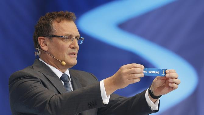 """Valcke holds up the slip showing """"Switzerland"""" during the draw for the 2014 World Cup in Sao Joao da Mata"""