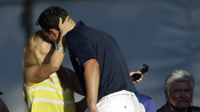 Justin Rose, right, of England, gets a kiss from his wife Kate after putting on the 18th hole during the fourth round of the U.S. Open golf tournament at Merion Golf Club, Sunday, June 16, 2013, in Ardmore, Pa. (AP Photo/Julio Cortez)