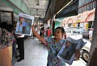 A local vendor is seen selling a journal with an image of democracy icon Aung San Suu Kyi and visiting US Secretary of State Hillary Clinton, at the Bogyoke market in central Yangon, on December 3. In one of a number of dramatic developments in Myanmar through the past year, Suu Kyi has said she will take part in by-elections expected early next year, although no date has been set