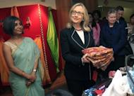 Us Secretary of State Hillary Clinton holds a sari during an Anti-Human Trafficking event in Kolkata. Clinton has called on India to further cut its imports of Iranian oil, saying New Delhi should use its growing clout to help isolate the Islamic republic