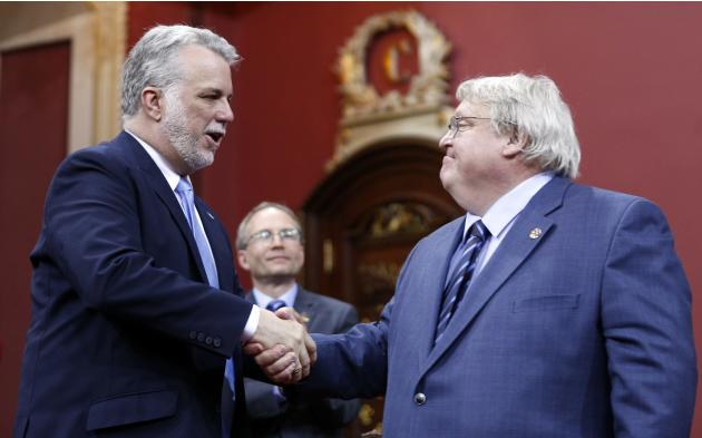 Quebec's Minister of Health Gaetan Barrette shakes the hand of Premier Philippe Couillard during a swearing-in ceremony at the National Assembly in Quebec City