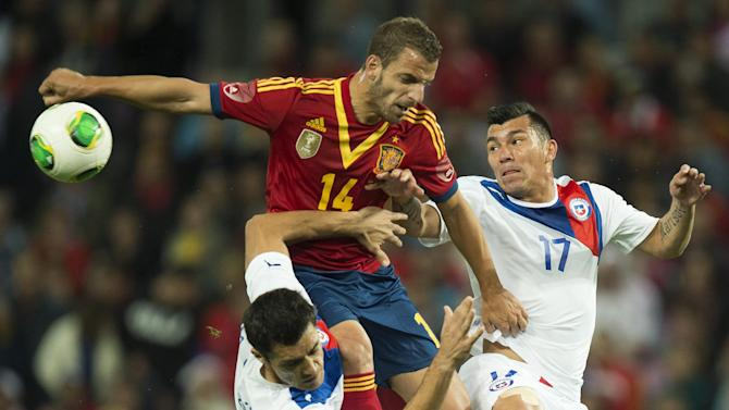 Spain's national soccer player Roberto Soldado, center, challenges for the ball with Chile's Marcos Gonzalez, left, and Gary Medel, right, during a friendly soccer match between Spain and Chile at the Stade de Geneve stadium, in Geneva, Switzerland, Tuesday, Sept. 10, 2013