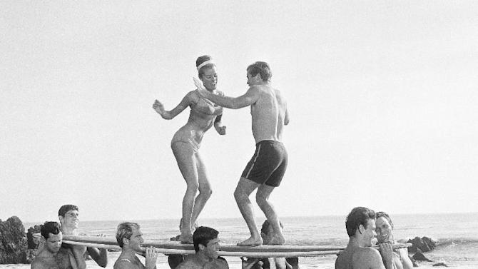 File-This 1965 file photo of youthful actors in a Hollywood movie amuse themselves between shooting of scenes at California's Malibu Beach by staging an airborne twist exhibition on top of a surf board. Annette Funicello helped create a world as fanciful as Walt Disney's Magic Kingdom when she traded in her Mousketeer ears for a modest one-piece bathing suit . It was a land of perfect waves and sparkling sand, in a place where there was a beach party every night and summer never ended. (AP Photo, File)