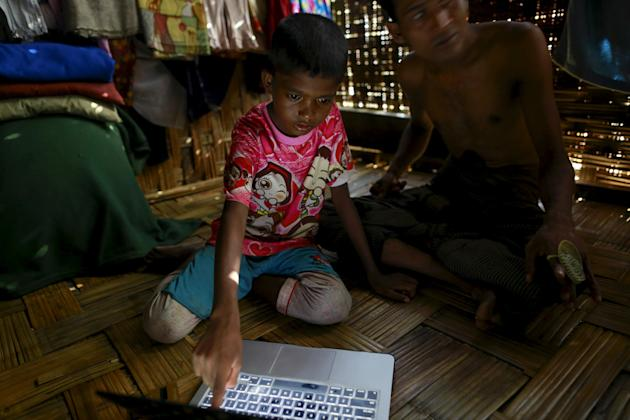 Cobiramou, 11, who was released from a human trafficking boat with his mother, points at pictures of people whom he recognises from the boat, at a refugee camp outside Sittwe