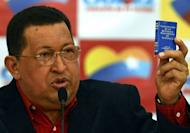 "Venezuelan President Hugo Chavez holds up a copy of the Constitution during a press conference in Caracas. Chavez has insisted he is ""totally"" cancer-free a little more than a year since he was diagnosed and said he was ready to take on a re-election battle"