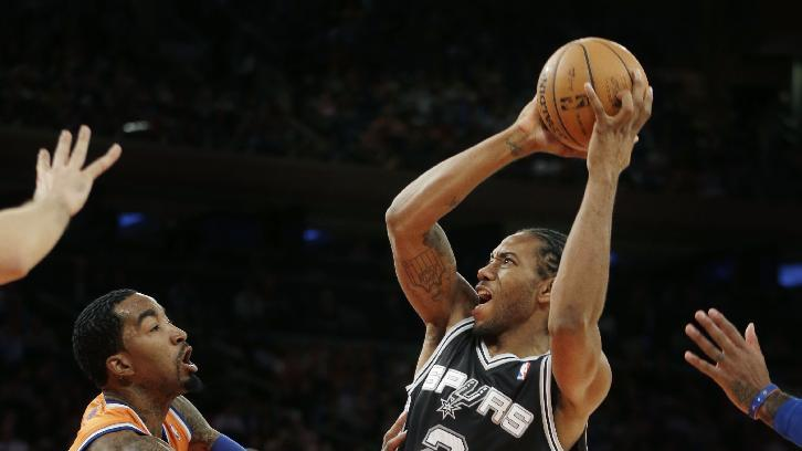 San Antonio Spurs' Kawhi Leonard, right, takes a shot over New York Knicks' J.R. Smith during the first half of the NBA basketball game at Madison Square Garden Sunday, Nov. 10, 2013 in New York
