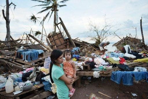 A woman and her child stand next to their destroyed house in Boston town, Davao Oriental province. Survivors of a typhoon that ravaged the southern Philippines will bypass Christmas this year as they hole up in evacuation centres and bury their dead, officials said Sunday.