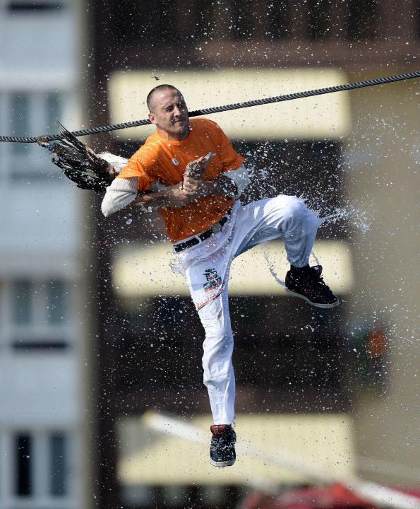 A man attempts to pull the neck off a dead goose while being repeatedly being plunged into the water during Antzar Eguna (Day Of The Goose) in the Basque fishing town of Lekeitio