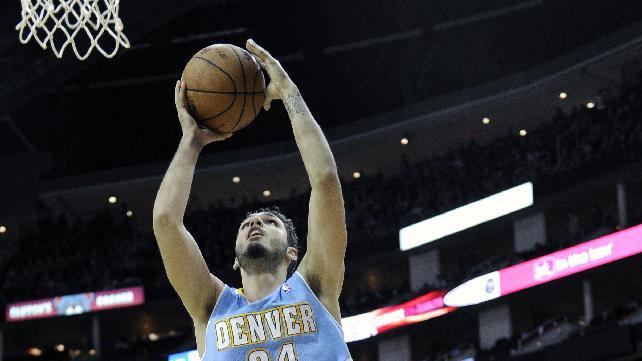 Denver Nuggets' Evan Fournier (94) goes to the basket between Houston Rockets Donatas Motiejunas (20) and Omri Casspi (18) in the first half of an NBA basketball game Saturday, Nov. 16, 2013, in Houston