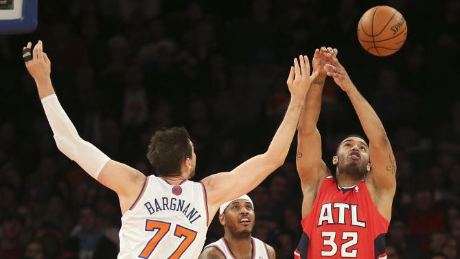 Atlanta Hawks forward Mike Scott (32) and New York Knicks forward Andrea Bargnani (77) battle for the ball as forward Carmelo Anthony (7) is near during the second half of an NBA basketball game Saturday, Dec. 14, 2013, in New York. The Knicks won 111-106
