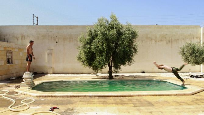 A Free Syrian Army fighter dives into a swimming pool, as his fellow fighter watches him in Aleppo