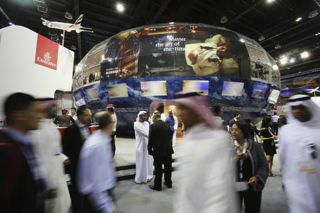 Visitors pass by the Emirates airline booth at the Arabian Travel Market exhibition in Dubai, United Arab Emirates, Tuesday, May 5, 2015. Sheikh Ahmed bin Saeed Al Maktoum, the top boss of the Middle
