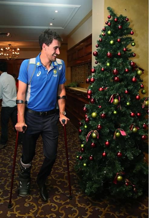 Australia's Mitchell Starc makes his way up past a Christmas tree using crutches after talking with the media following their cricket test against New Zealand in Adelaide, Australia, Monday, Nov.