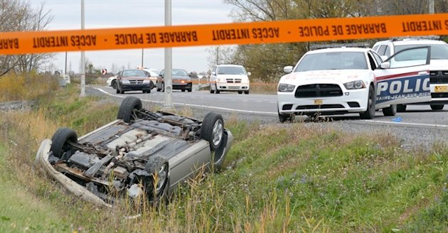 A car is overturned in the ditch in a cordoned off area in St-Jean-sur-Richelieu, Que. on Oct. 20, 2014.