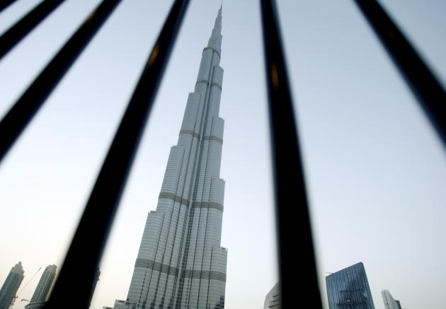 A view of the Burj Khalifa tower is seen in downtown Dubai, in this May 10, 2011 file photo. In September 2012, Abu Dhabi, the capital of the United Arab Emirates, a federation of seven Gulf emirates, told state employees that if they lived outside its city limits they would not be eligible for housing allowance, which accounts for about a third of their salaries. The government has said the new rule was aimed at cutting traffic and road accidents, a nod to the risk of commuting on the busy desert highway between Abu Dhabi and Dubai. But analysts and industry experts say the policy is designed to help absorb a glut of new high-end homes in Abu Dhabi and revive state developers such as bailed-out Aldar. The Abu Dhabi government declined to comment on the rulings implications for the property market. REUTERS/Jumana El-Heloueh/Files (UNITED ARAB EMIRATES - Tags: SOCIETY EMPLOYMENT BUSINESS)